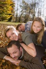 Familie liegt auf Blättern im Herbst, Portrait