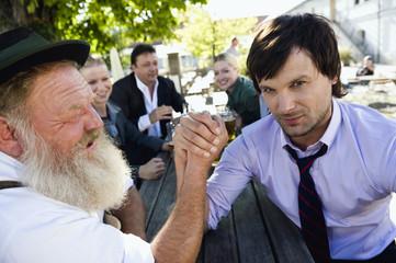 Deutschland, Bayern, Oberbayern, Zwei Männer im Biergarten beim Armdrücken