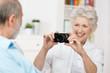 lachende seniorin fotografiert ihren mann
