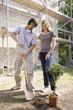 Junges Paar auf der Baustelle einen Baum pflanzend