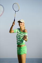 Junge Frau spielt Badminton am Strand