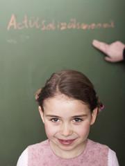 Mädchen stehen vor Tafel, Schule