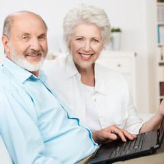 lachendes älteres ehepaar am laptop