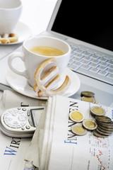 Tasse Kaffee, Cookie Euro, Münzen, Zeitung und Handy vor Laptop
