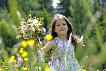 Mädchen mit Blumenstrauß auf Wiese, lächelnd, Nahaufnahme