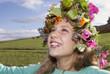 Mädchen trägt Kranz aus Blumen, lächelnd