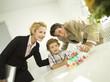 Junge Familie, Vater zündet Kerzen auf Geburtstagskuchen an