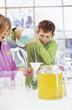 Jungen und Mädchen im Labor, Junge gießt Flüssigkeit