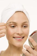 Junge Frau zupft ihre Augenbrauen, Portrait