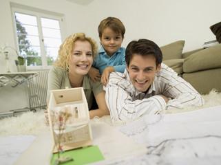 Junge Familie im Wohnzimmer, lächelnd, Porträt