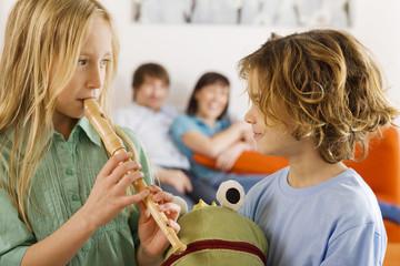 Junge und Mädchen, sie spielt Blockflöte