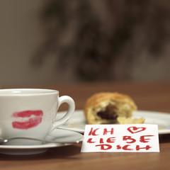 Tasse Kaffee mit Lippenstift Kussabdruck, angebissenes Croissant und ein lieber Zettel