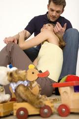 Junges Paar sitzt auf dem Boden mit Spielzeug