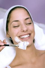 Junge Frau mit Gesichtsmaske mit Make-up-Pinsel, lächelnd, Nahaufnahme