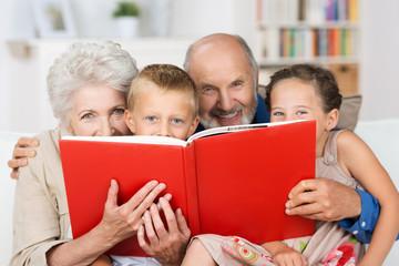 großeltern und enkel schauen hinter einem buch hervor