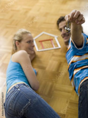 Paar auf dem Boden liegend, hält Schlüssel
