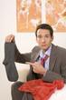 Mann sitzt auf dem Sofa, mit Socken in der Hand, Portrait