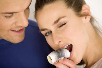 Junges Paar, Frau, essen Rollmops