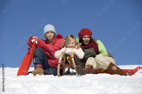 Österreich, Mädchen sitzen mit Schlitten im Schnee, lächelnd, Porträt