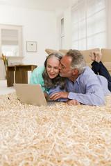 Junges Paar liegt auf dem Teppich mit Laptop, Mann küssen Frau