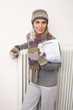 Frau hält Stromrechnung, trägt Schal und Mütze, teure Energiepreise