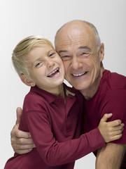Enkel umarmt Großvater, Lächeln, Portrait