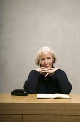 Seniorin sitzt am Tisch mit Buch, Portrait