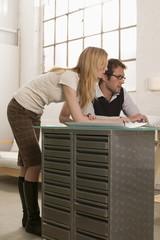 Junger Mann und junge Frau arbeiten am Schreibtisch
