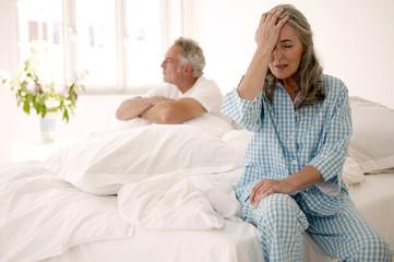 Älteres Paar sitzt auf dem Bett