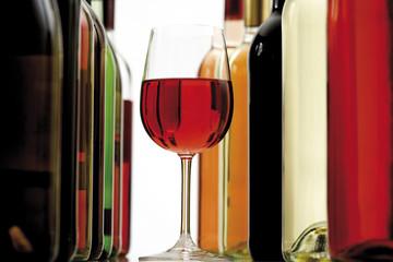 Glas Rotwein zwischen Weinflaschen, Nahaufnahme