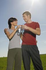 Junges Paar prostet sich zu mit Wasserflasche lächelnd