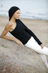 Junge Frau stützte sich auf Felsen am Strand, Wegsehend, Seitenansicht