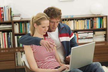 Junges Paar sitzt auf dem Stuhl, mit Laptop