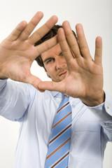 Junger Geschäftsmann bildet Rahmen aus Fingern, Portrait