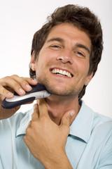 Junger Mann, Rasieren mit elektrischem Rasierer, Nahaufnahme, Portrait