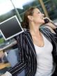 Geschäftsfrau mit Telefon im Büro, lachend, Nahaufnahme