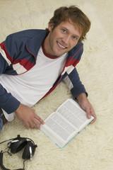 Junger Mann auf dem Boden liegend, Buch lesend