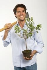 Junger Mann mit Topfpflanze und Spaten, Nahaufnahme
