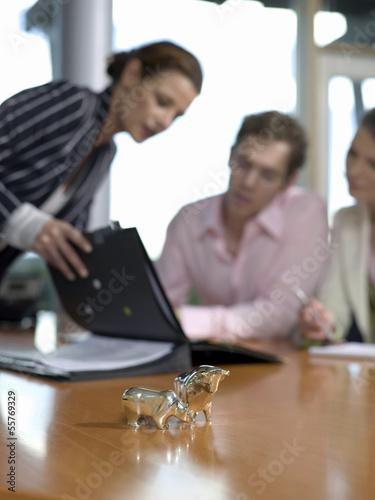 Geschäftsleute im Büro bei der Arbeit, Figuren von Bulle und Bär auf dem Schreibtisch