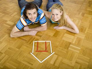 Paar auf dem Boden liegend, mit Blick in die Kamera