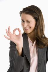Geschäftsfrau, die OK-Zeichen macht, blinzelnd, Portrait, Nahaufnahme