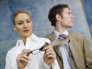 Geschäftsfrau, reinigt Brille mit Krawatte eines Kollegen