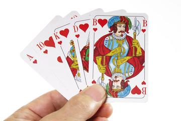 Person hält Royal Flush mit Herz auf der Hand
