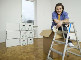 Mann lehnt sich an Leiter, mit Pinsel