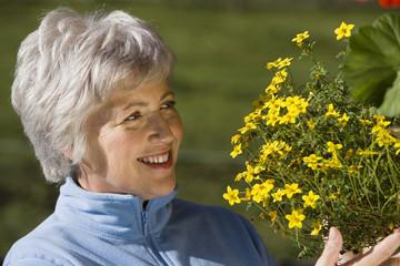 Österreich, Seniorin schaut Blumen an