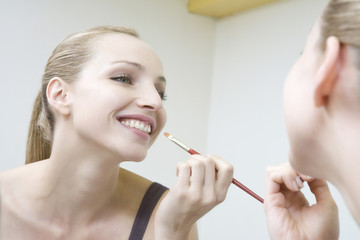 Junge Frau beim Auftragen von Lippenstift, Lächeln, Portrait
