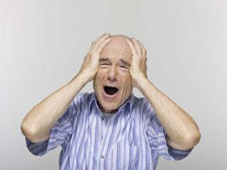 Älterer Mann mit den Händen über Stirn, Portrait