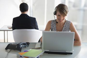 Geschäftsfrau mit Headset arbeitet am Laptop, männliche Kollegen im Hintergrund