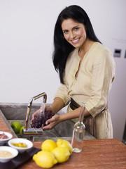 Frau wäscht Trauben in Spüle, lächelnd