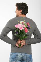 Junger Mann mit Blumenstrauß hinter dem Rücken, lächelnd, Rückansicht